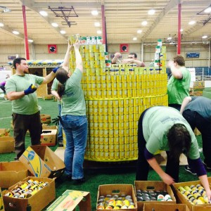 "Members and friends of St. Dunstan's take apart a giant Lego head build of canned goods, as cleanup helpers for the 2014 ""Canstruction"" event benefiting Middleton Outreach Ministry."